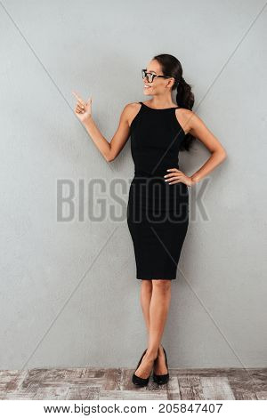 Full length portrait of a happy young businesswoman in black dress and eyeglasses standing and pointing finger away at copy space isolated over gray background