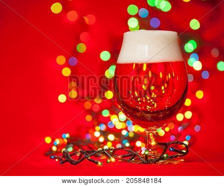 Full snifter glass of lager of pilsner beer with christmas lights on red background