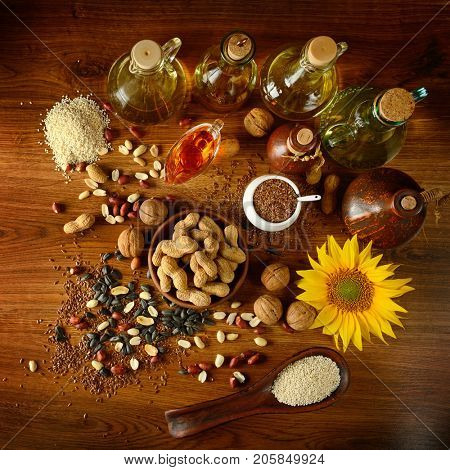 Still life seeds and oils useful for health (Flax, sesame, sunflower, olives, walnut, peanuts). Top view. Wooden background.