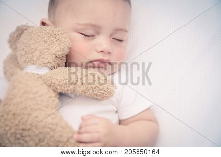 Cute little baby in the bed, adorable infant sleeping with little bear, nice little boy in the morning, healthy childhood, peace and relaxation concept