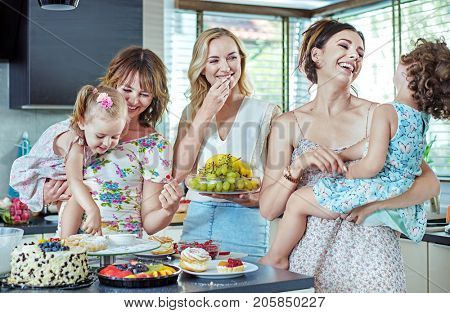 Young mothers cooking with their little children in the kitchen