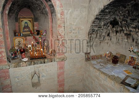 Cave Temple An Orthodox monk with burning candles and icons