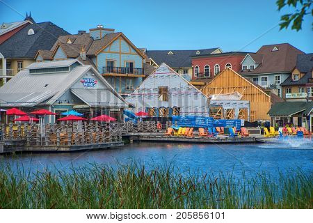 COLLINGWOOD, ON, CANADA - JULY 19, 2017: View of businesses and restaurants by a recreational pond at Blue Mountain Village, Ontario's only four season mountain resort.