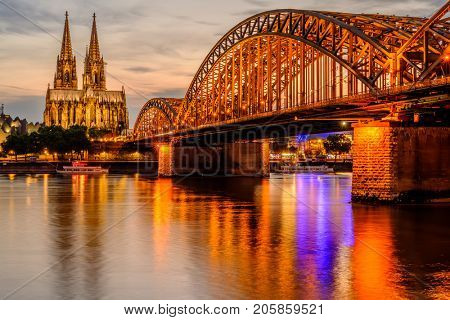 Night View of Cologne Cathedral (Kolner Dom) and Rhine river under the Hohenzollern Bridge at sunset, Cologne city skyline at night, North Rhine Westphalia region, Germany.