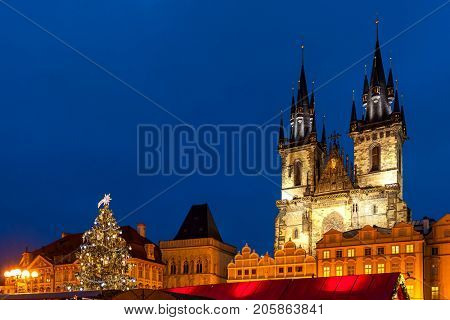 Illuminated Tyn church and Christmas tree on Old Town Square under evening sky in Prague, Czech Republic.