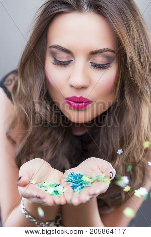 Happy Caucasian Brunette Woman Holding New Year Confetti in Hands And Blowing Them Around. Against Gray Background.Vertical Image