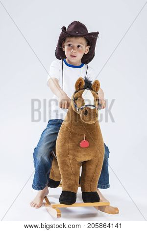 Kids Consepts. Caucasian Expressive Boy in Cowboy Clothing Posing With Symbolic Plush Horse Against White. Directing Forward. Vertical Image Composition