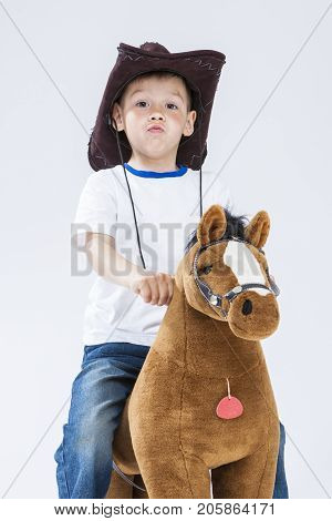 Kids Consepts. Portrait of Proud and Arrogant Caucasian Little Boy in Cowboy Clothing Posing With Symbolic Plush Horse Against White. Vertical Image Composition