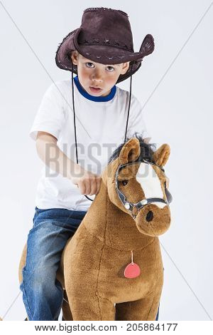 Kids Consepts. Caucasian Expressive Boy in Cowboy Clothing Posing With Symbolic Plush Horse Against White. Directing Forward. Vertical Shot