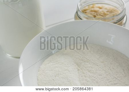 Bowl of semolina with milk bottle on white background