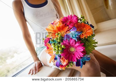Bride with a bride t-shirt garter and a colorful bouquet. She's taking a break before getting her dress on!