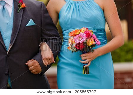 An orange pink red yellow bouquet being held by a bridesmaid wearing a blue dress walking down the aisle with a groomsman.