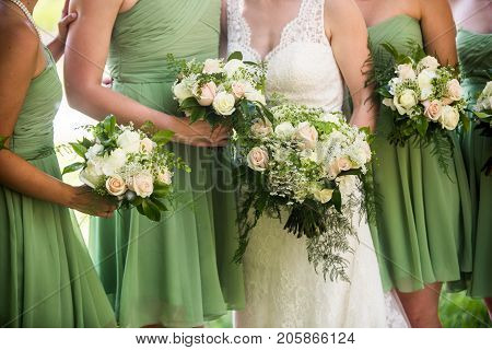 A candid photo of bride and her bridesmaids wearing light green bridesmaid dresses and holding a gorgeous bouquet. White and pink roses with baby's breath and green accents.