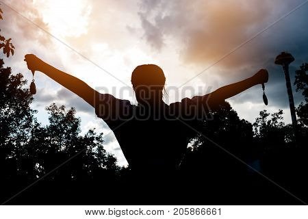 Blurred of silhouette businesswoman hands raised and holding gold medals with ribbon against sunset background to show team success in business Winners success award concept.