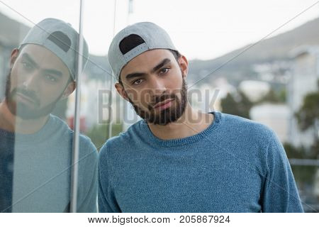 Portrait of man leaning on glass