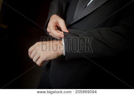 Caucasian man wearing a tuxedo fixing his cufflink.