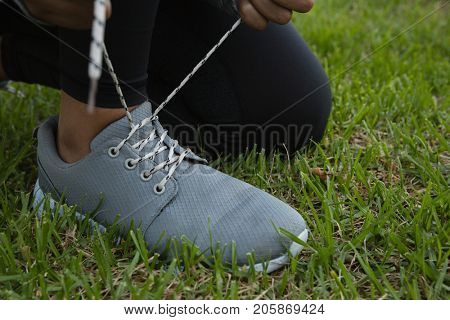 Low section of female athlete tying shoelace while kneeling on field