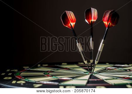 Red black and green dartboard on its side with three fiery metal tipped darts in the bulls eye. On black background.
