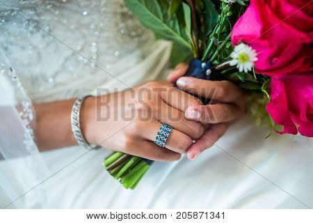Beautiful closeup of an ethnic brides's blue and silver ring on the hands of a beautiful ethnic bride.