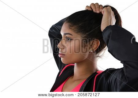 Young female athlete looking away while tying hair against white background