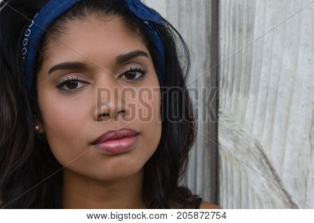 Close up portrait of confident young woman against wooden wall