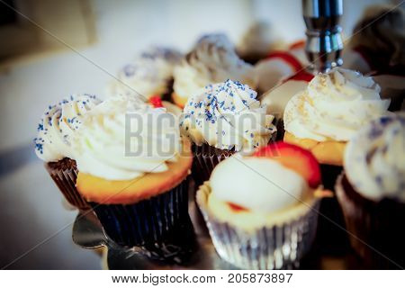 Selective focus on middle cupcake. Shallow depth of field. Various cupcakes on a tray ready to be served.