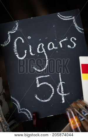 Simple black retro chalkboard sign offering cigars.