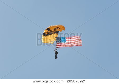 A Member Of The U.s. Army Golden Knights Parachute Team Flys The American Flag