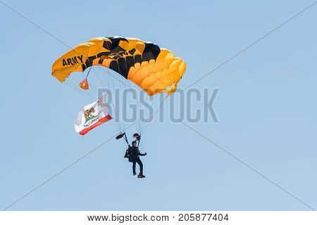 A Member Of The U.s. Army Golden Knights Parachute Team Flys The Californian Flag