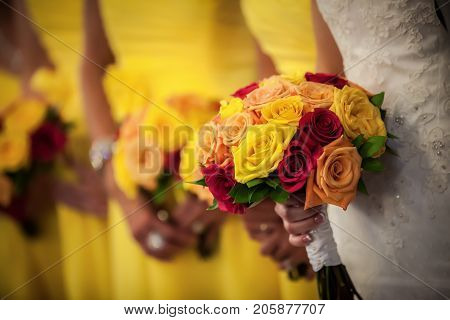 Beautiful bride holding red yellow orange bouquet with bridesmaids in the background.