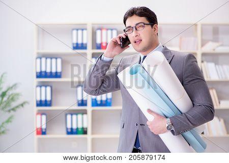 Businessman engineer draftsman with blueprints drawings