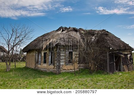 Abandoned Russian village. Ruins of rural house with thatched roof