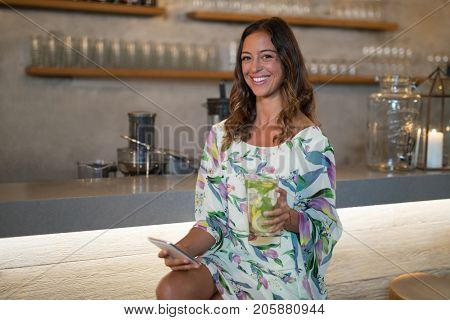 Portrait of beautiful woman using mobile phone while having mocktail