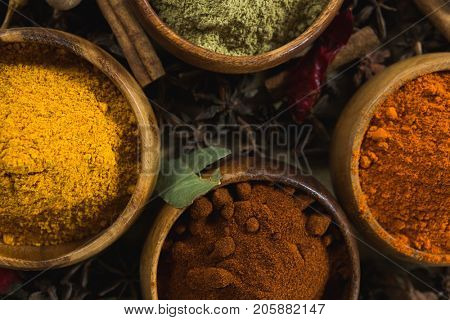 Close-up of various spice powder in wooden tray