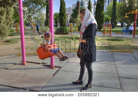 Fars Province Shiraz Iran - 19 april 2017: Playground in a city recreation park a young muslim woman wearing a hijab swings little boy on a swing.