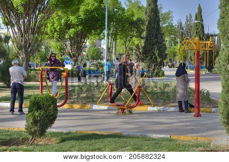 Fars Province Shiraz Iran - 19 april 2017: Outdoor playground free exercise machines Muslim women in hijabs do the morning exercise.