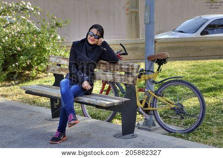 Fars Province Shiraz Iran - 19 april 2017: One fashionable young muslim woman wearing sunglasses and hijab smiling sitting on a bench in the city park next to her bicycle.
