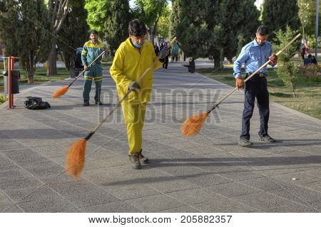Fars Province Shiraz Iran - 19 april 2017: Three janitors sweep the road in the city recreation park using brooms.