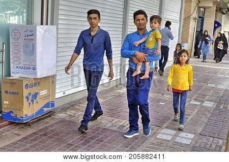 Fars Province Shiraz Iran - 19 april 2017: A mature Iranian man walks along the sidewalk of a city street with three children.