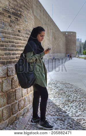 Fars Province Shiraz Iran - 19 april 2017: A teenage girl in a Muslim hijab stands at the wall of Karim Khan Castle and listens to music from a smartphone using earphones.