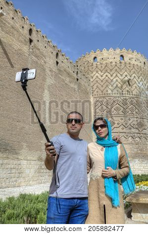 Fars Province Shiraz Iran - 19 april 2017: Young Iranian pair photographing himself against the walls of the ancient castle using selfie stick and smartphone.