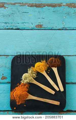 Overhead view of various spice powder in wooden spoon
