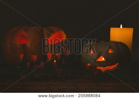 Illuminated jack o lantern with candles in darkroom during Halloween