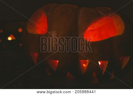 Close up of jack o lantern glowing in darkroom during Halloween