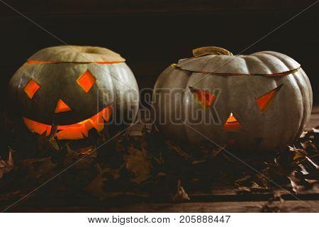 Close up of illuminated kack o lanterns with autumn leaves arranged on table