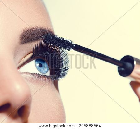Mascara Applying. Long Lashes closeup. Mascara Brush. Eyelashes extensions. Makeup for Blue Eyes. Eye Make up Apply, Eyebrows shaping. Beautiful woman eyes make-up