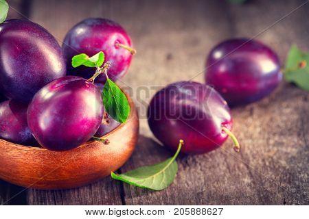 Plum. Healthy juicy ripe organic plums fruit close-up, on wooden table. Prune. Sweet dessert