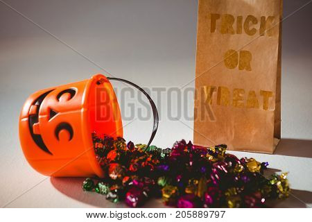 Trick or treat text on paper bag by bucket and colorful chocolates on white background