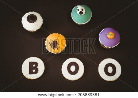 High angle view cookies with boo text by cup cakes over black background