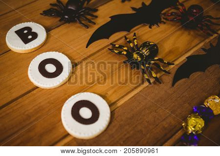 High angle view of cookies with boo text by decorations on wooden table